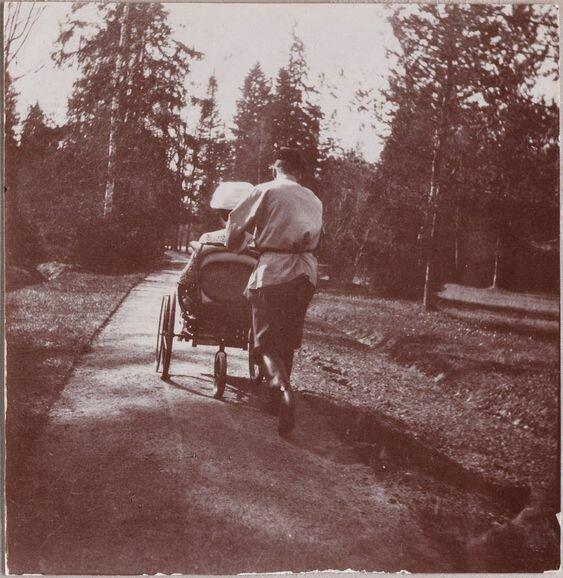 Russian Tsar Nicholas II is taking his wife in a wheelchair for a walk.